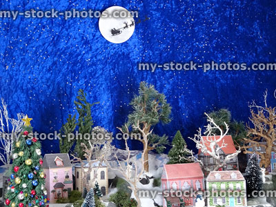 stock image of christmas village display with model paper houses flying santa
