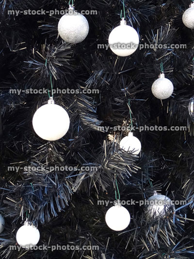 stock image of artificial black christmas tree with white baubles silver decorations monochrome christmas