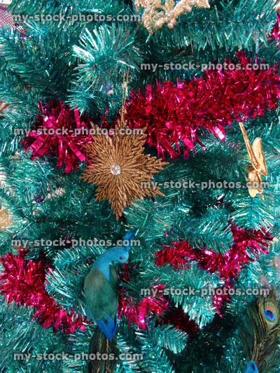 Stock image of tinsel Christmas tree, green / turquoise peacock, gold flowers, butterfly