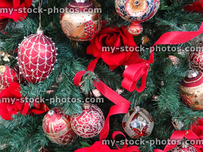 stock image of artificial christmas tree red rose decorations baubles ribbons and berries